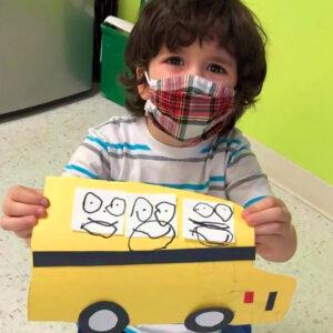 A pre-k boy show off his schoolbus artwork