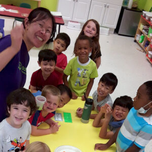 A group of pre-k students and their teacher smile for a photo at snack time