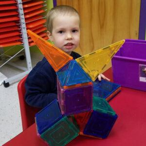 Preschool Boy plays with magnet blocks