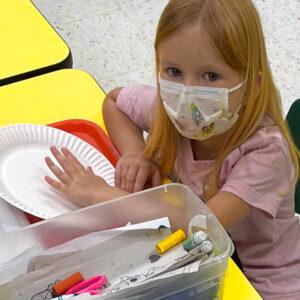 Preschool girl with drawing materials begins an art project