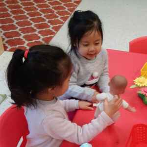 Two preschool girls playing with dolls at a table