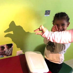 Preschool girl uses a light to make finger puppets on the wall
