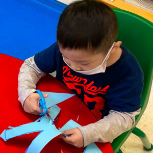 Preschool Boy practices cutting paper with scissors