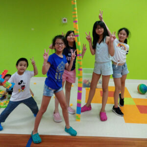 A group of children showing off their massive tower of duplo bricks