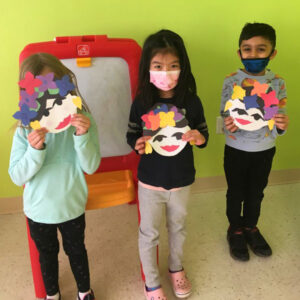 Boys and girls show off artwork they created after school at Kiddosland