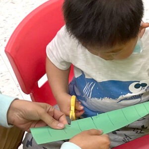 young boy leaning to use scissors