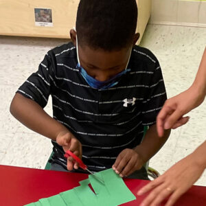 Boy cutting paper at Kiddosland