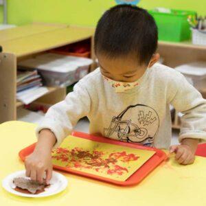 preschool boy making leaf prints with orange paint on construction paper
