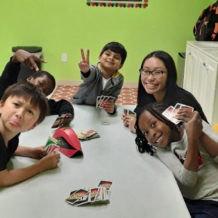 Group of kids playing a card game after school at Kiddosland