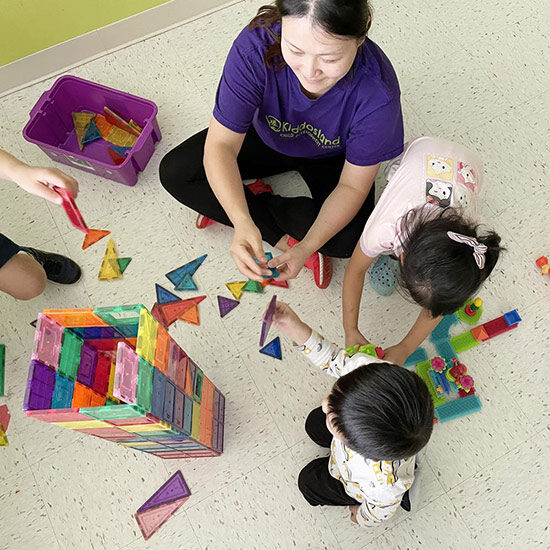 3 children with teacher building a tower out of colorful magnet tiles