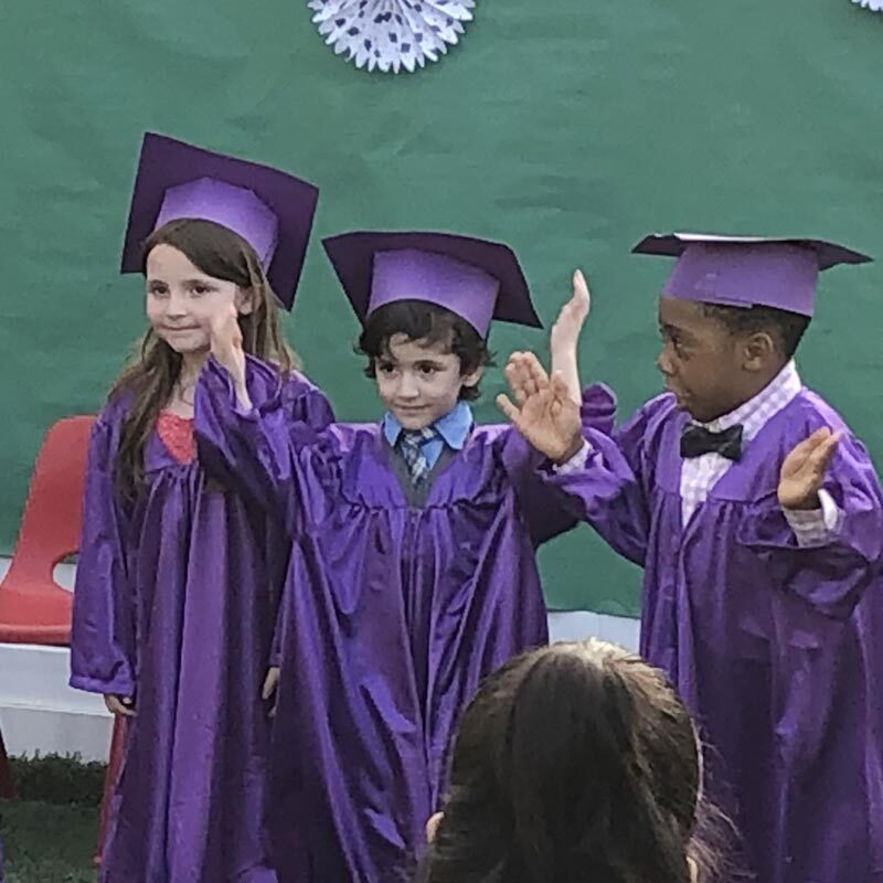 Three 5-year-olds in purple caps and gowns excited about kindergarten