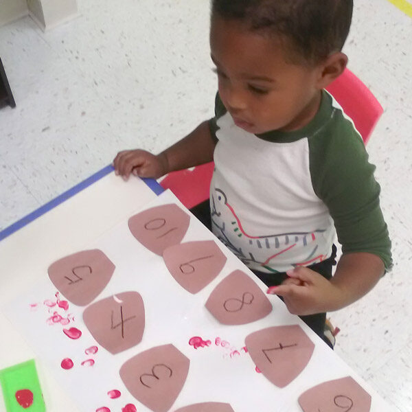 Mikey learning his numbers by making an art project at Kiddosland