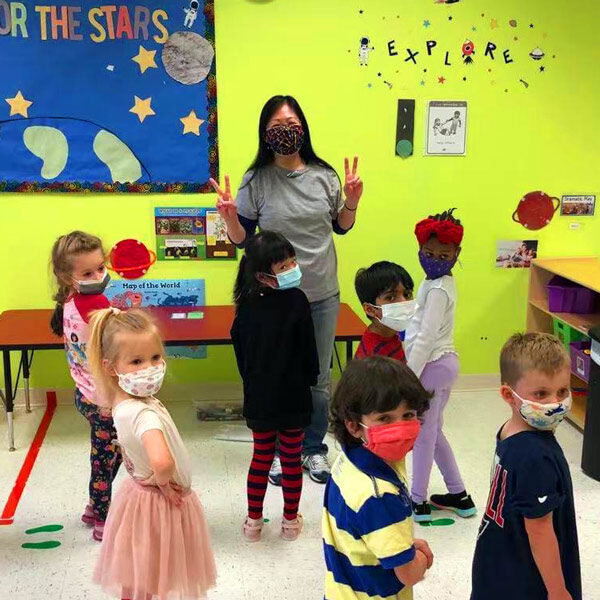 A pre-k teacher and students pose for a photo at circle time