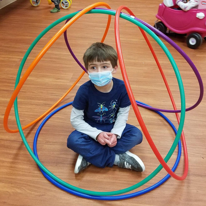 A pre-k boy sits in a cirle of hula hoops.