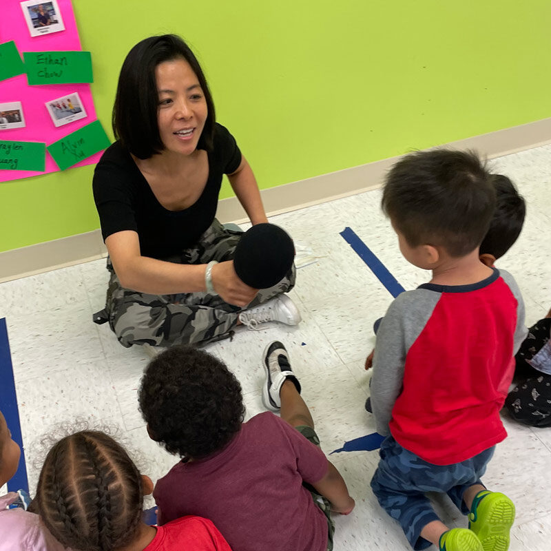Teacher and kids at circle time learning mandarin and english at a dual-language preschool