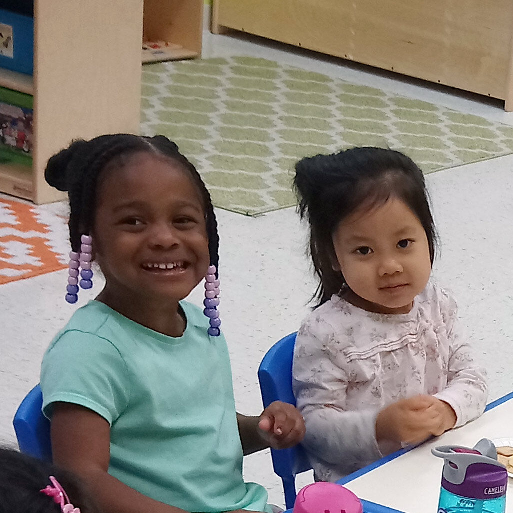 Two preschool girls pose for a photo