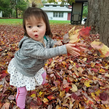 Toddler playing in the fall leaves