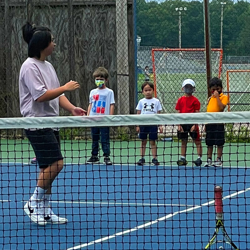 Students learning to play tennis